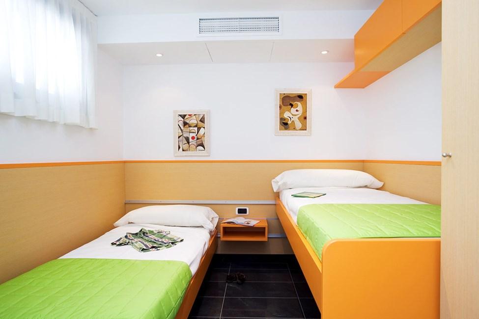 Ett av sovrummen i en trerumslägenhet med 2 ordinarie bäddar