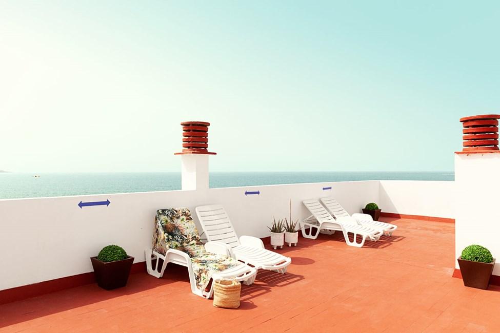 Hotellets takterass med solstolar och fin utsikt över havet