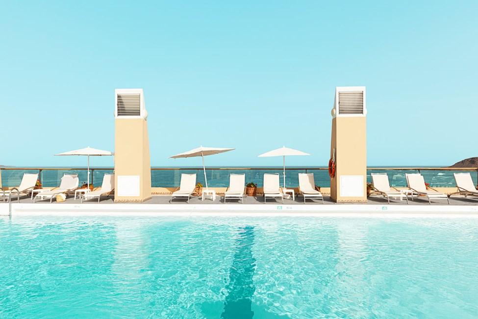 Runt poolen finns gott om solstolar och parasoll.