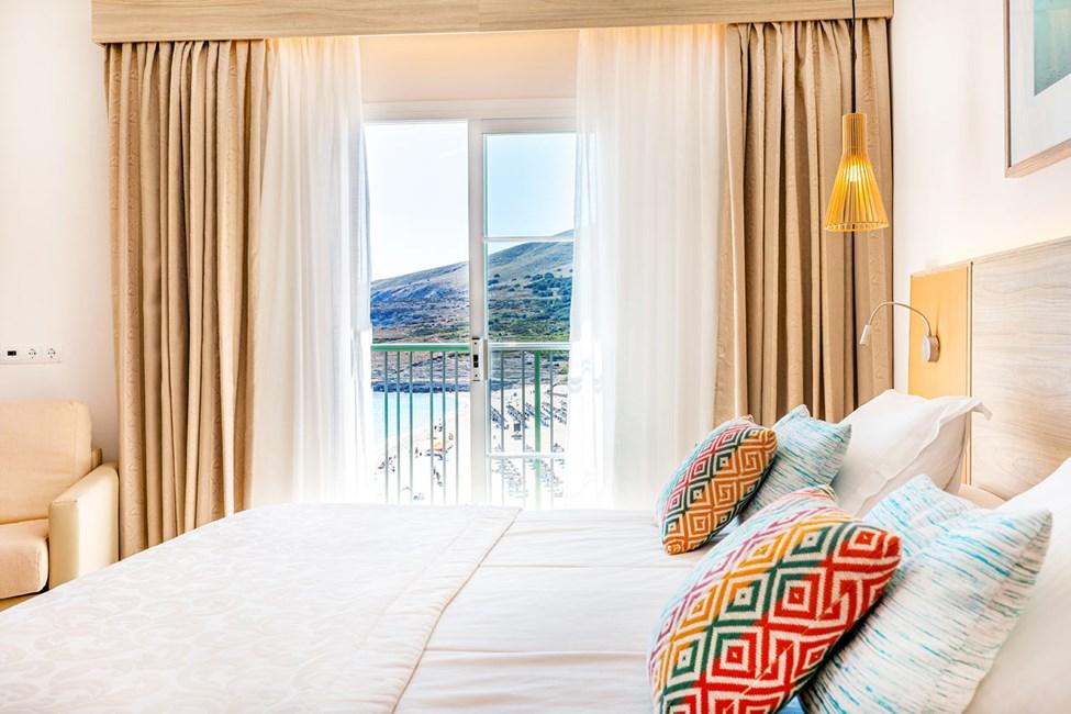 Sovrum i tvårumslägenhet med havsutsikt, tvårumslägenhet med stor takterrass och begränsad havsutsikt samt tvårumslägenhet med begränsad havsutsikt och privat trädgård